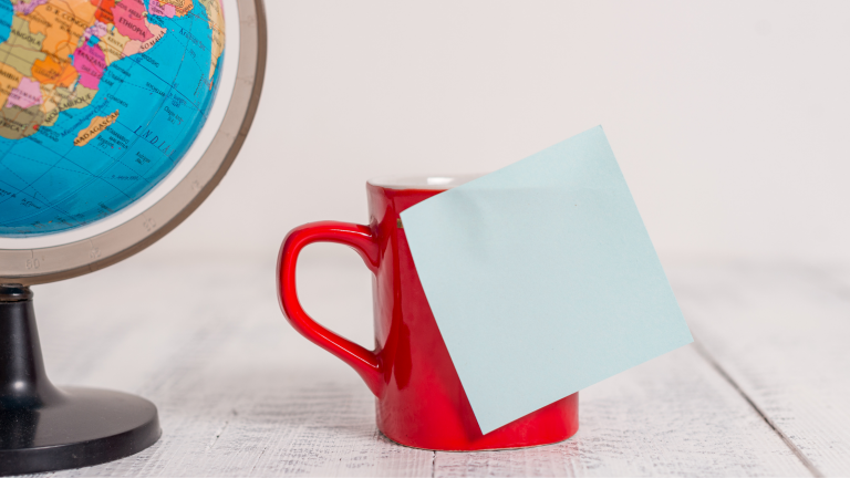 Image shows a globe, and a red mug with a post-it note stuck to it.